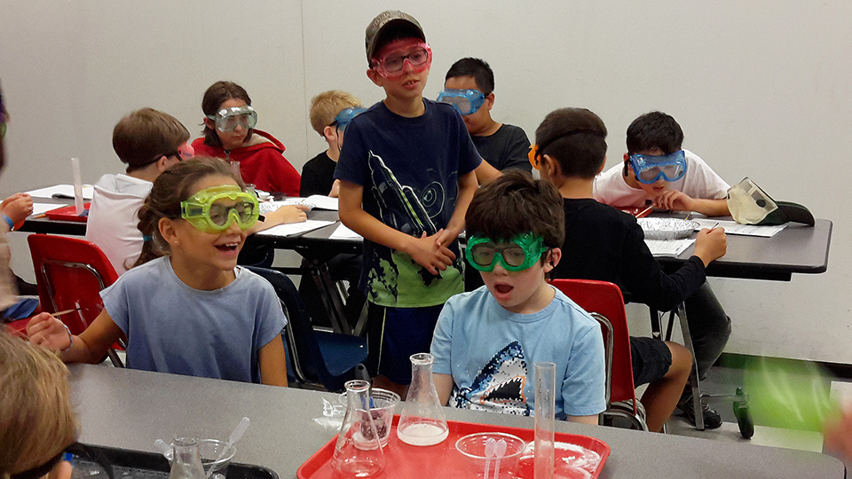 Campers prepare an experiment using beakers.