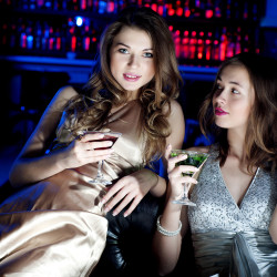two hot girls in club having cocktails and inviting SHT