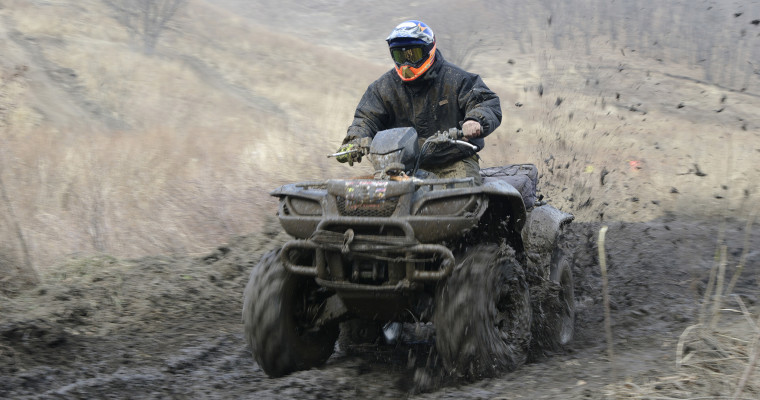 quad or atv being driven off road through the mud SHT