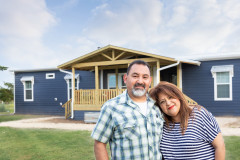 Couple standing in front of their Custom Clayton built home
