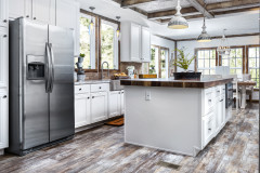 Farmhouse style kitchen with white cabinets, hardwood style vinyl floor and stainless steel appliances.
