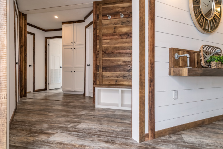 An open entryway with floor to ceiling white cabinets and natural wood features.