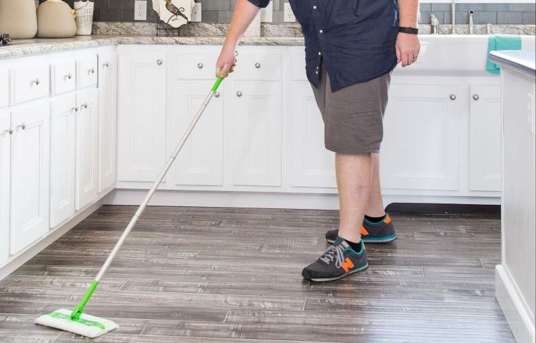 Man cleaning vinyl wood style floors in the kitchen of a manufactured home.