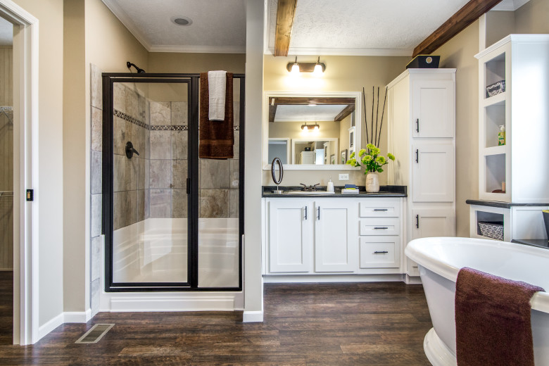 Primary bathroom of the Lloyd with walk-in shower, vanity and built-in storage.