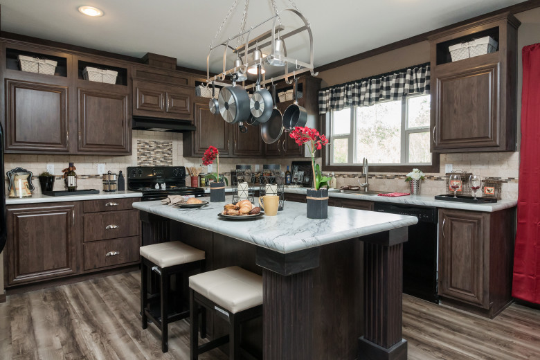 Manufactured home kitchen with dark wood styles cabinets and a breakfast bar.