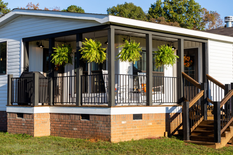 A Clayton Built® home with a covered front porch and ferns hanging down.