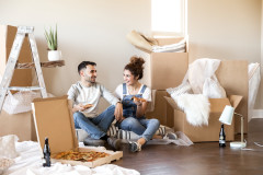 Young couple eating pizza on the floor of their manufactured home with boxes around.