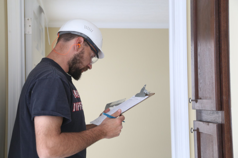 Man wearing T-shirt and hard hat looks at clipboard while inspecting a manufactured home.