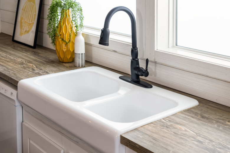 White, double basin farmhouse sink with black faucet, light wood counters with white and yellow decor and two windows behind it.