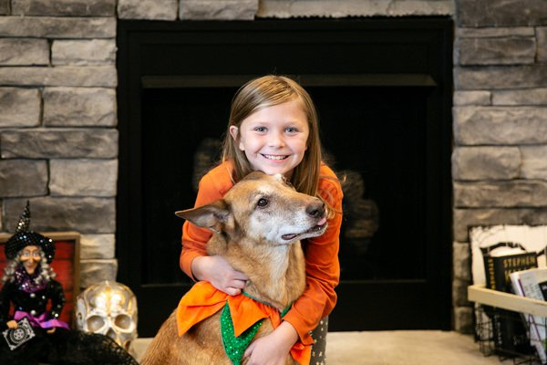 Young girl in her new home sitting on fireplace hearth with her dog