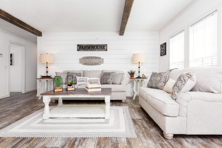 Farmhouse styled manufactured home with white shiplap walling and wide plank wood floors.