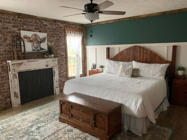 Primary bedroom with green accent wall, white bed, brick accent wall and fireplace.