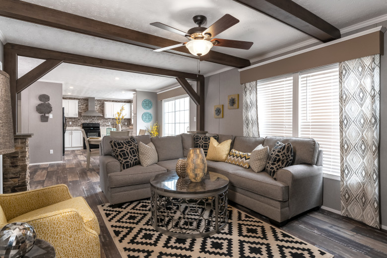 Manufactured home living room with ceiling beams and large windows.