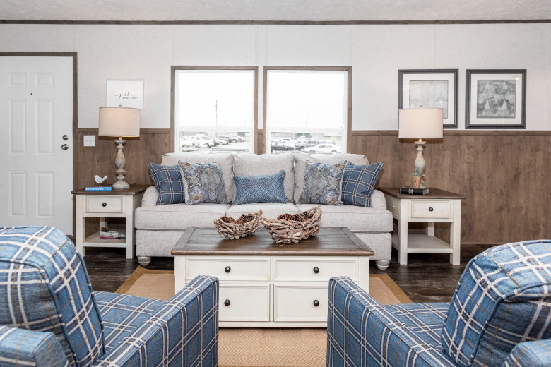 Living room of manufactured home with two blue plaid chairs, a white couch and farmhouse style furniture.