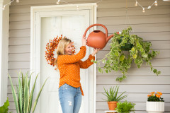 Women water her hanging plant outside her manufactured home.