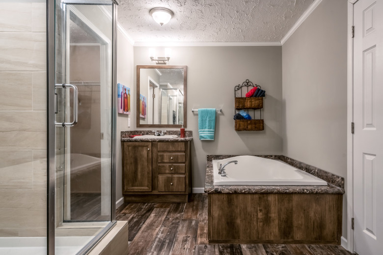 Large manufactured home bathroom featuring a large bathtub that has wood grain accents around it and a walk-in shower.