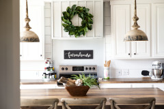 Farmhouse styled manufactured home with white cabinets and wood styled counter tops.