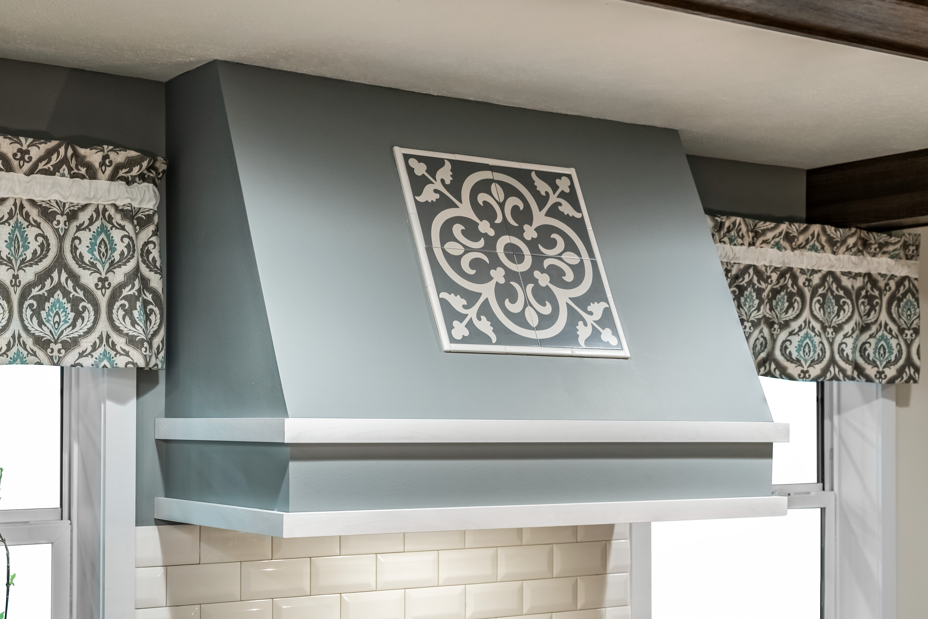 Mobile home kitchen with a large range hood with lace designs on it.