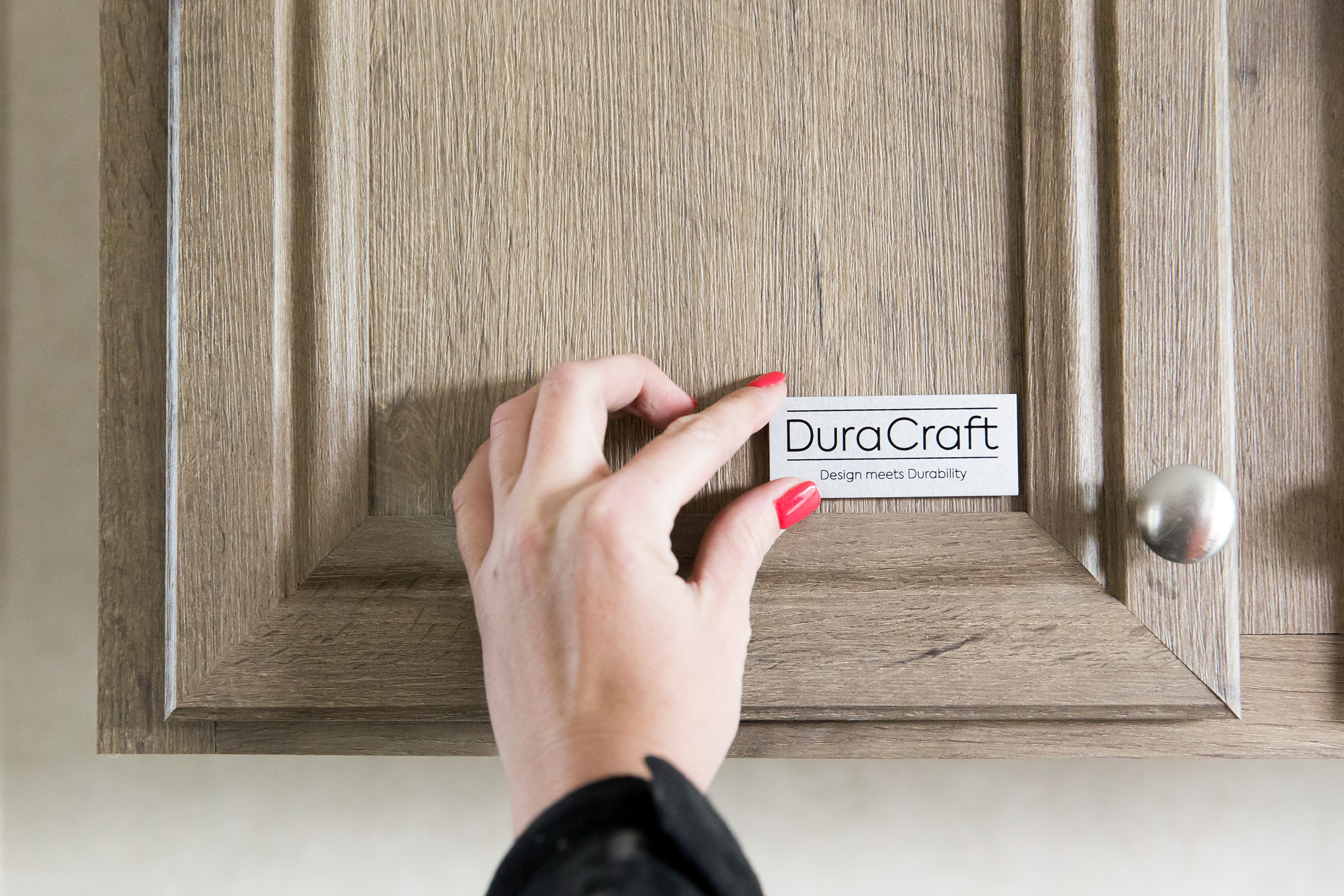 Hand putting DuraCraft logo sign on light colored cabinet.