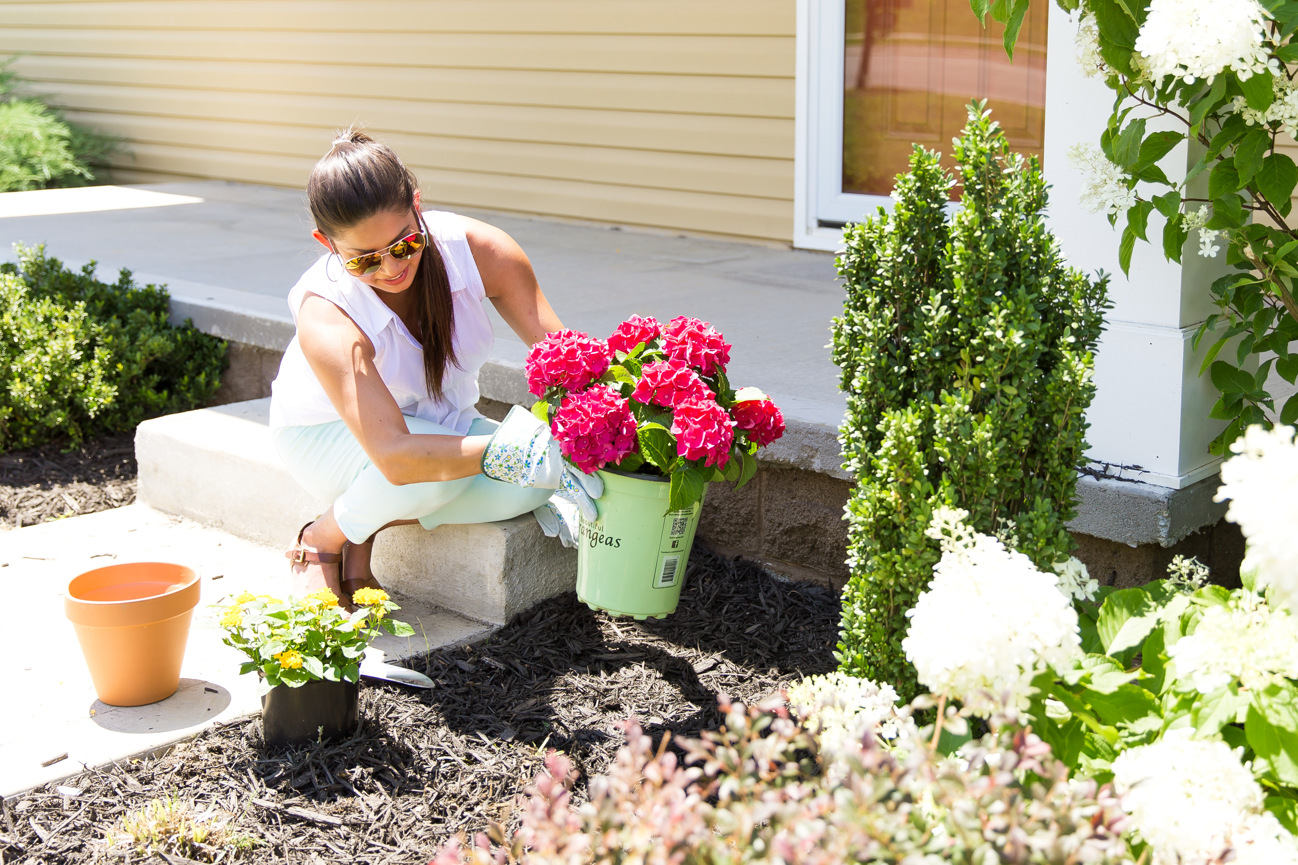 Woman adding a front lawn garden outside her manufactured home.