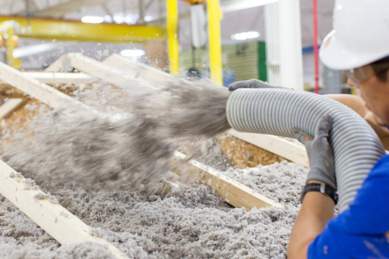 A worker at a building facility blows insulation into the roof cavity of a manufactured home.