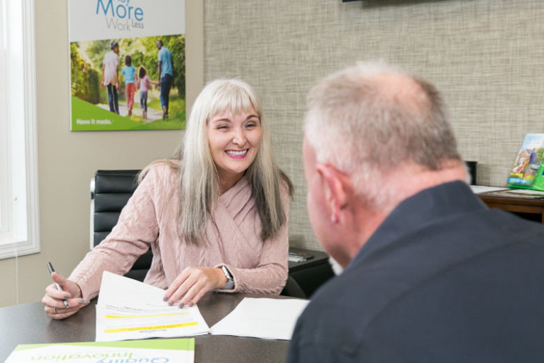 Woman in pink sweater sitting in a chair smiles at man as she signs paperwork at table in a home center.