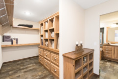 A walk-in closet connecting to the primary bathroom with built-in cubbies, drawers and shelving.