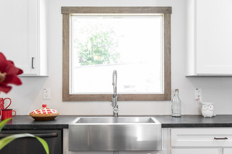 Picture of a silver basin farmhouse sink settled into black counters in front of a large window feature.