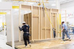 Two team members work to assemble wall of manufactured home inside a home building facility.