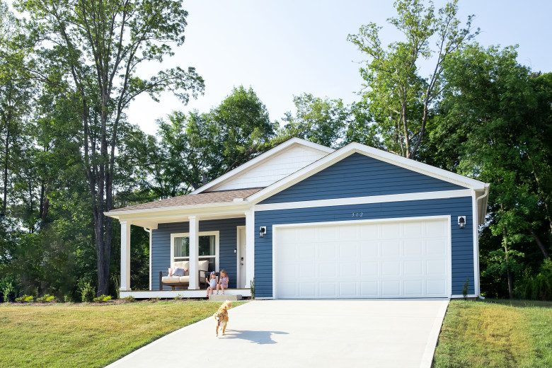 Blue new class Clayton home with golden retriever running down the driveway in front of the white garage door