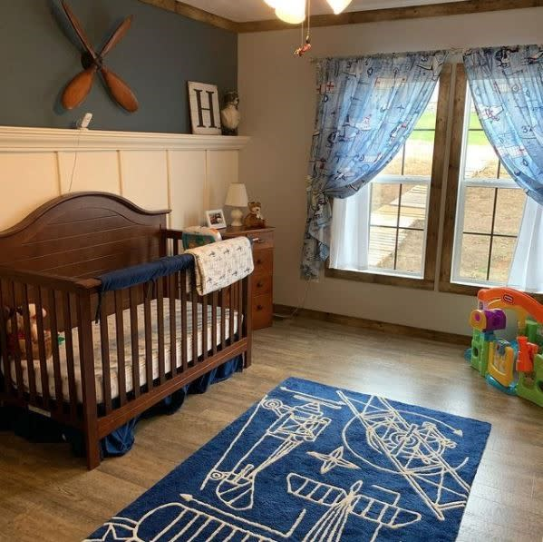 Nursery with dark wood crib and table, white wainscotting, dark green wall, blue rug and light blue curtains.