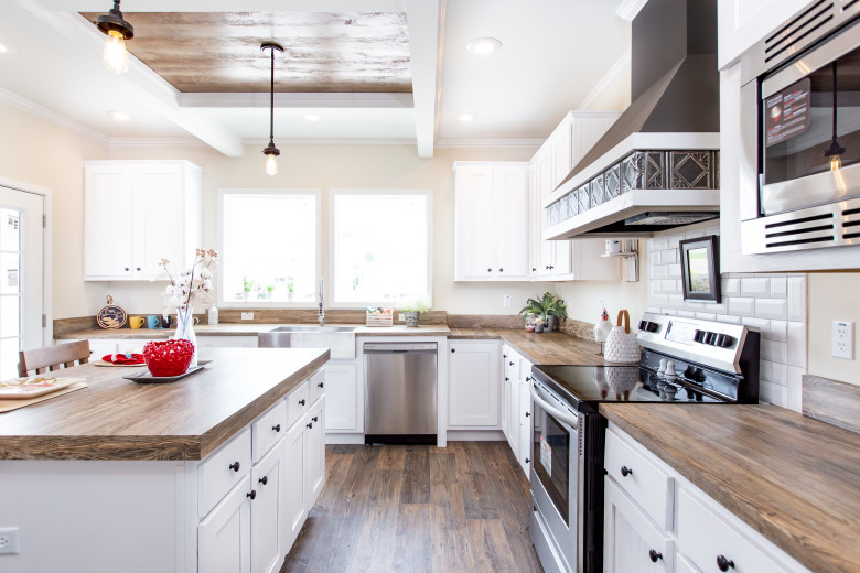 Kitchen of the Southern Charm model featuring white cabinetry and wooden countertops.