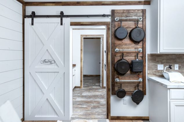 A large farmhouse style pantry in a manufactured home with a sliding white barn door and hanging cast iron skillets.