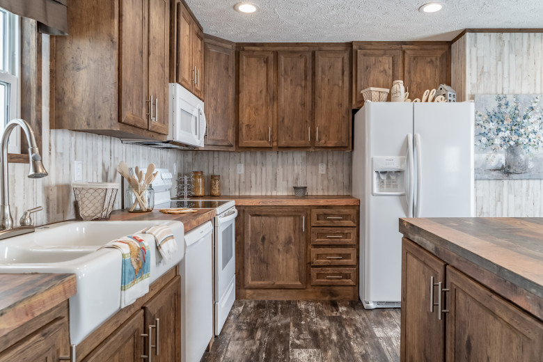 Manufactured home kitchen with wooden cabinets and a kitchen island.