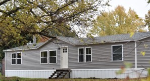 Grey double wide prefab home with front steps and white door.