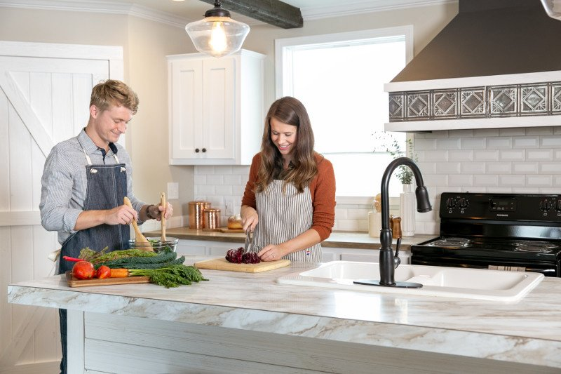 Couple cooking together in their manufactured home kitchen on large island.