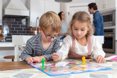 A young boy and girl playing a board game while their parents are in the kitchen.