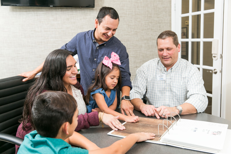 A dad, mom, little girl and little boy looking at flooring with a home consultant.