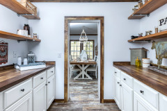 Manufactured home walk-in pantry with white cabinetry.