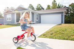 Child riding a red tricycle on the sidewalk outside a blue manufactured house.