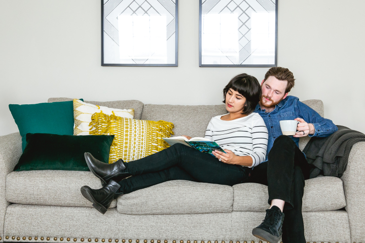 Couple reading a book in the living room of their manufactured home.