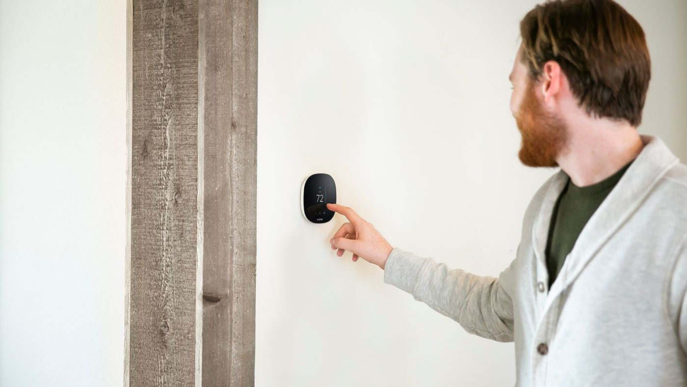 Person adjusting their smart thermostat inside a manufactured home.