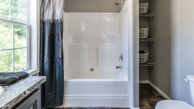 A manufactured home bathroom that features a shower tub combo along with a storage area to the side of it.