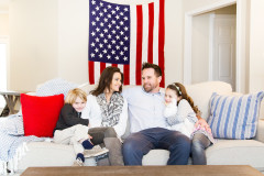 Parents and two kids sit on a couch with American flag behind them.