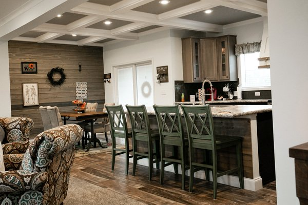 Fountain family manufactured home kitchen and dining area with oversized island, plank wall and farmhouse table