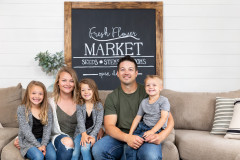 Family sits on couch in farmhouse living room in front of a shiplap wall.