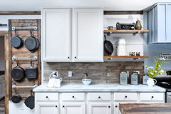Farmhouse kitchen with wood grain hanging rack holding cast iron skillets, white cabinets, marble style countertops, and stone backsplash.