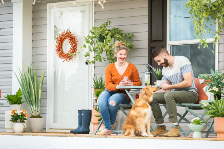 Man and woman on patio furniture with a dog on the front porch of a tan manufactured home, surrounded with plants.