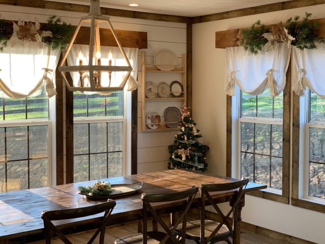 Dining room with wooden table, wooden chairs, large windows and farmhouse decor.
