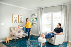 Woman standing next to crib with child and man sitting in chair in manufactured home nursery.